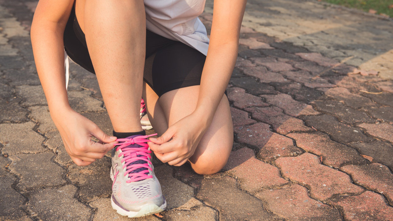 Woman tying shoelaces before a run.