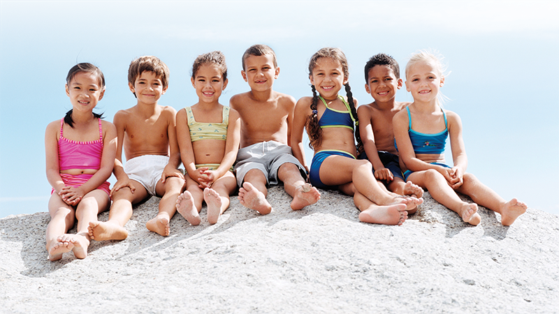 Kids sitting on a sand hill