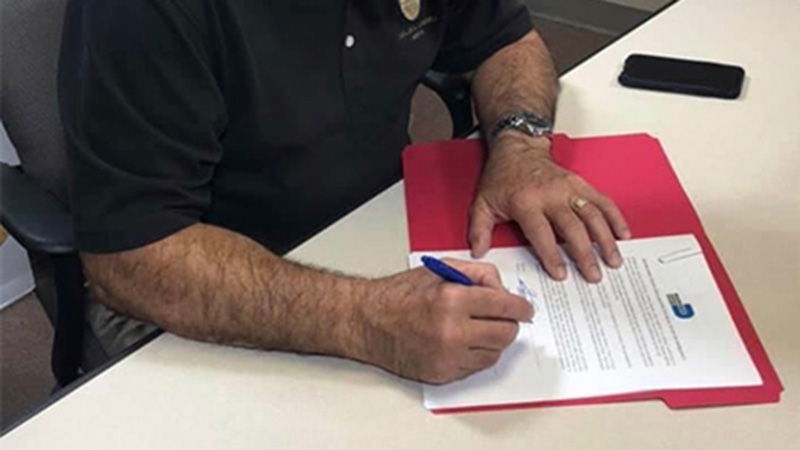 The Mayor signs the executive order.